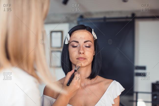 Makeup artist applying model's foundation before photo shoot