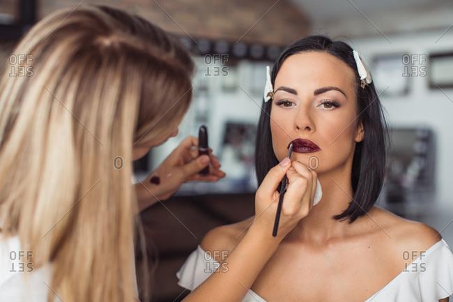 Makeup artist applying model's lipstick before photo shoot
