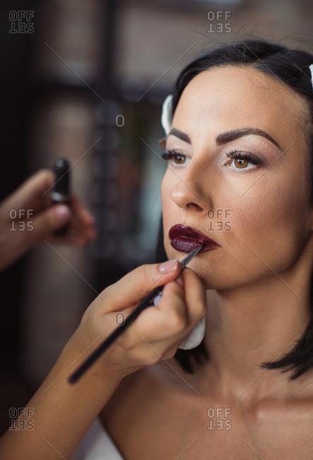 Makeup artist applying model's makeup before photo shoot