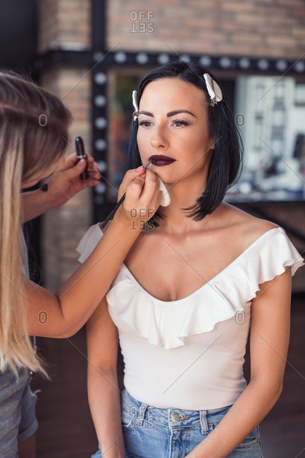 Cosmetologist applying model's lipstick before photo shoot