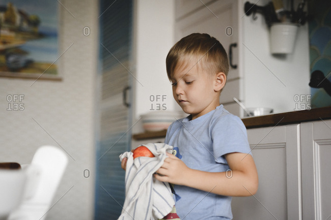 Portrait of little boy drying peach with kitchen towel