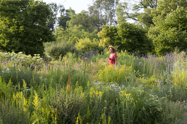 Woman wearing straw hat and red summer dress in garden with wildflowers