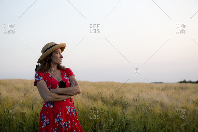 Woman wearing straw hat and red summer dress with floral design standing in front of grain field
