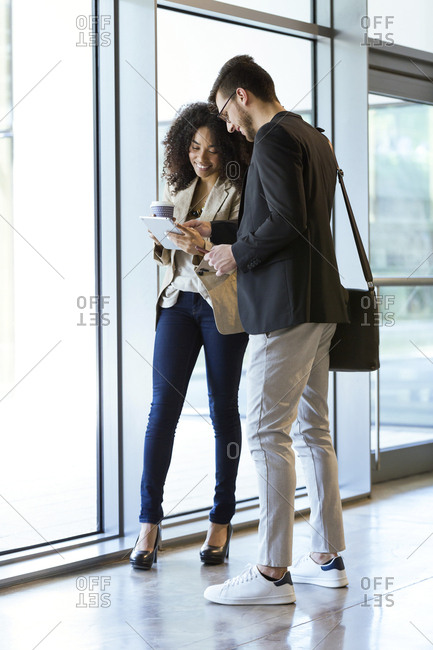 Two young business partners using a tablet in a hallway