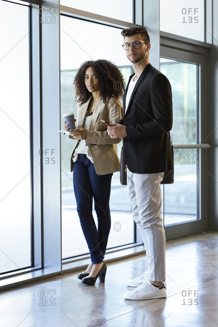 Portrait of two young business partners standing in a hallway