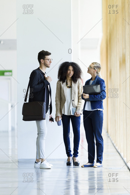 Young business people talking in a hallway