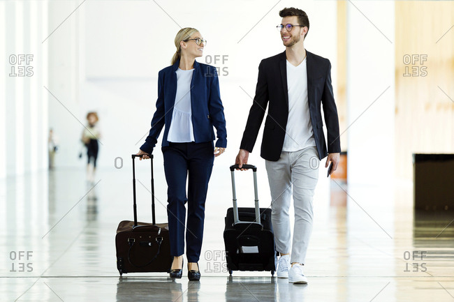 Two smiling young business partners walking at the airport