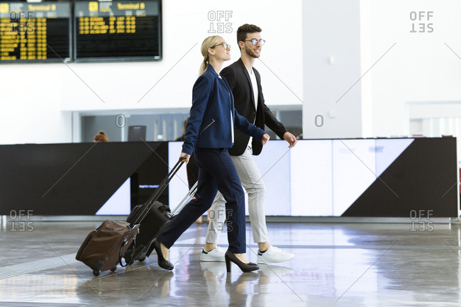Two young business partners walking at the airport