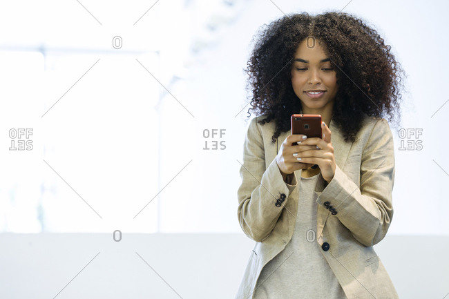 Smiling young businesswoman using a smartphone