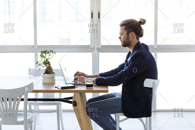 Businessman using laptop at table in modern office
