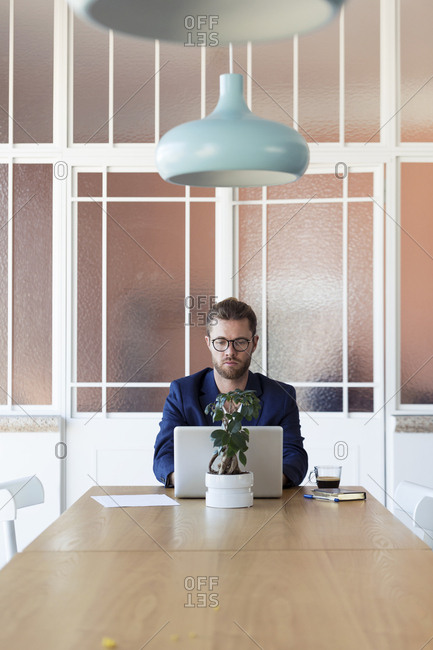 Businessman with laptop at table in office