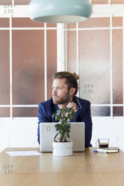 Pensive businessman with laptop at table in office