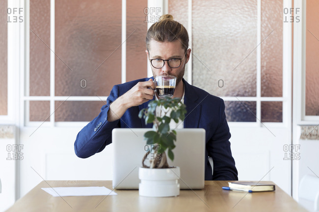 Businessman with laptop and cup of coffee at table