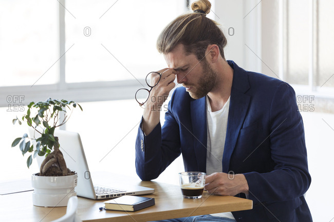 Tired businessman sitting at table in office