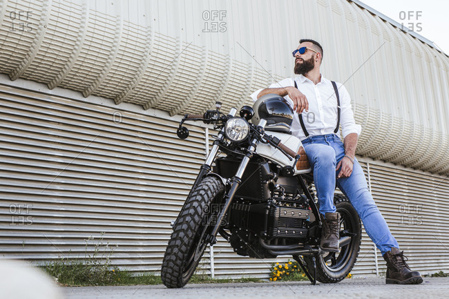 Bearded motorcyclist with sunglasses leaning on his motorbike