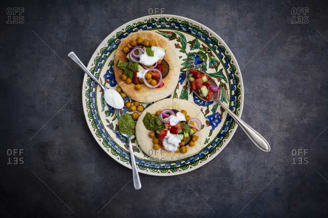 Garnished Sabich- pita bread with fresh vegetables- onions- yogurt and sauce