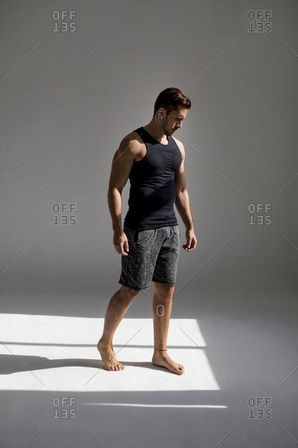 Athlete standing in sunlit studio