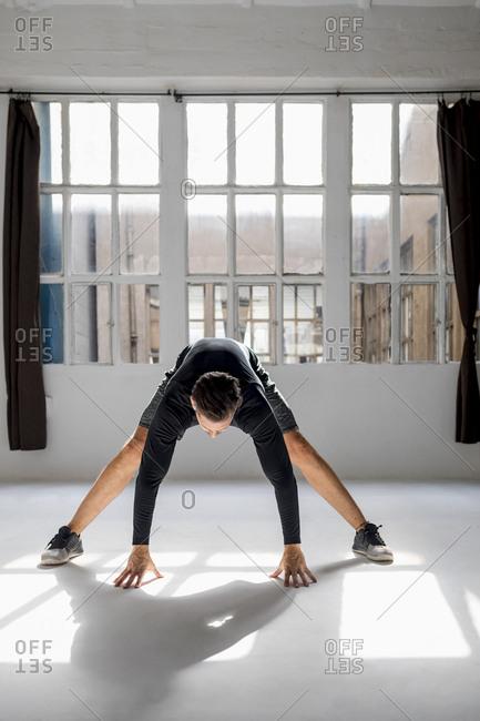 Athlete worming up in sunlit studio