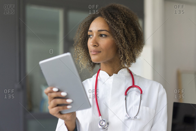 Portrait of young doctor with stethoscope and digital tablet looking at distance