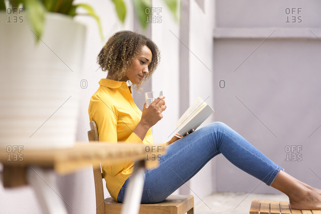 Young woman relaxing with glass of water reading a book