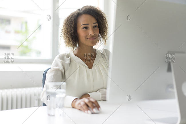 Portrait of smiling young freelancer working at desk