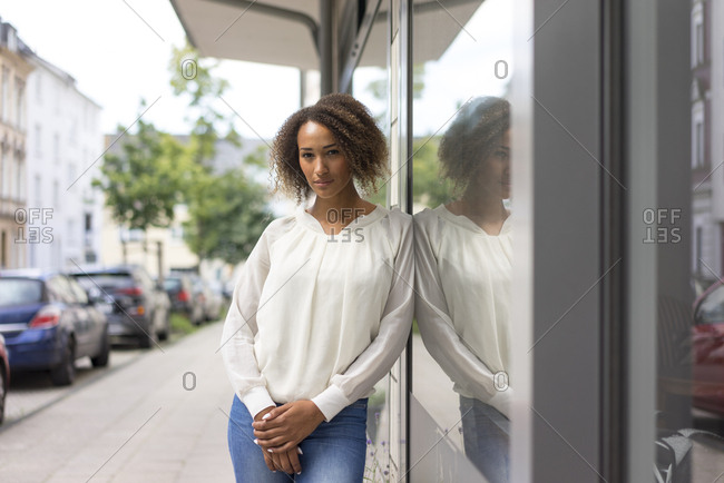 Portrait of young woman leaning against window display