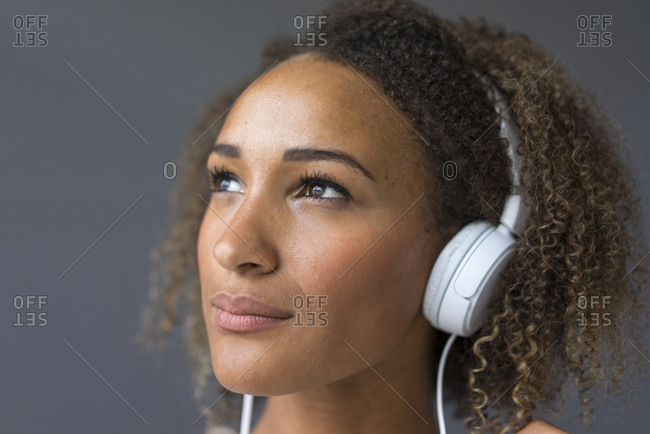 Portrait of young woman with white headphones looking up