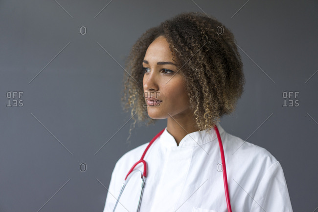 Portrait of young doctor with stethoscope in front of grey background