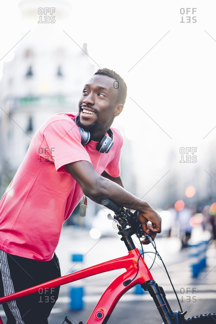Happy young man with e bike in the city