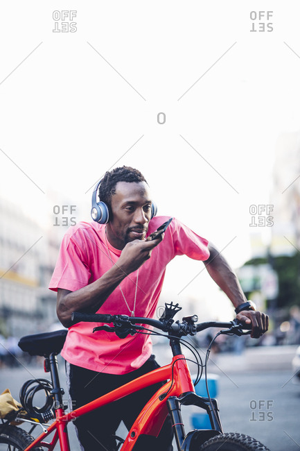Young man with e bike and headphones using smartphone in the city