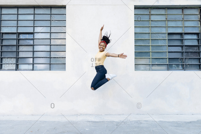 Happy young woman jumping in the air in front of white wall