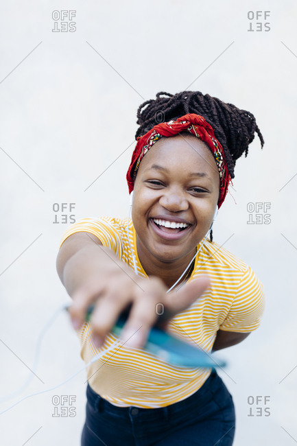 Portrait of happy young woman listening music with headphones and earphones in front of white wall