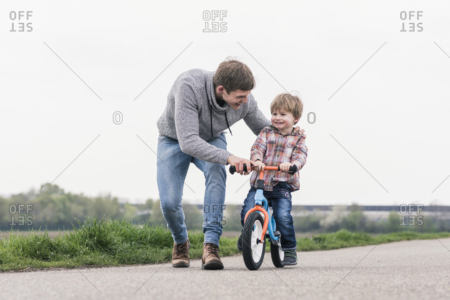 Father teaching his son how to ride a bicycle- outdoors