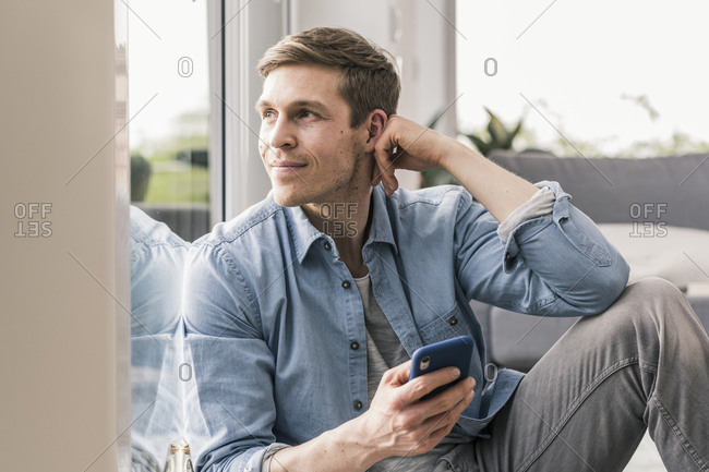 Mid adult man sitting by window- using smartphone