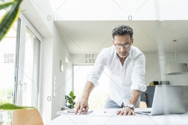 Architect working on blueprint in a bright office- using laptop