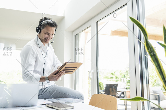 Businessman in bright office having conference call- using headset and digital tablet