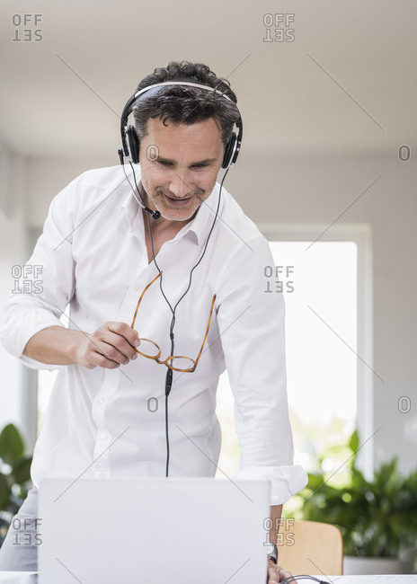 Businessman in bright office having conference call- using headset and laptop