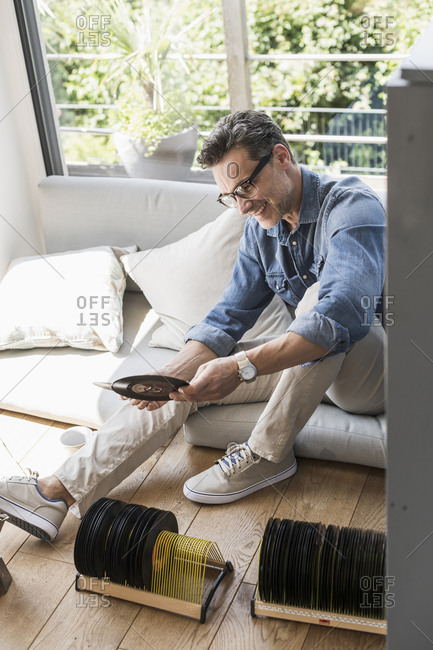 Mature man sitting at home- looking at vintage single records
