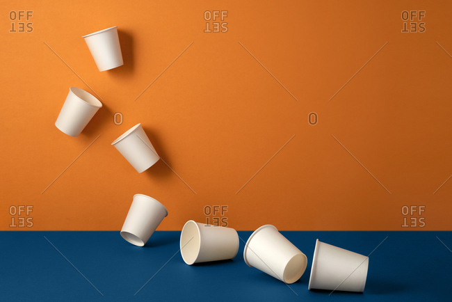 Disposable plastic white empty cups on blue and orange background