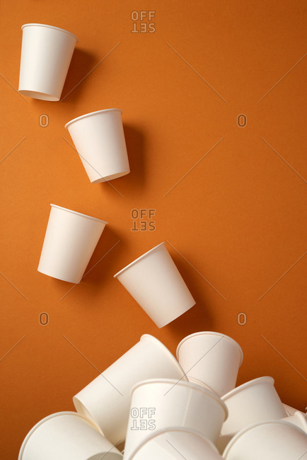 top view of white plastic cups on orange background with copy space