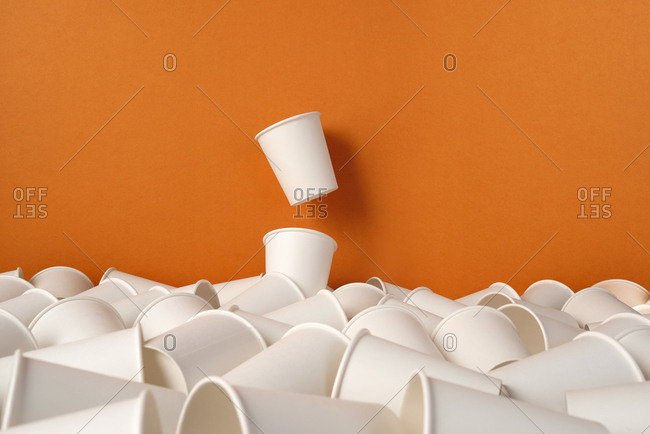 Disposable paper cups arranged pattern on orange background, recyclable paper cups
