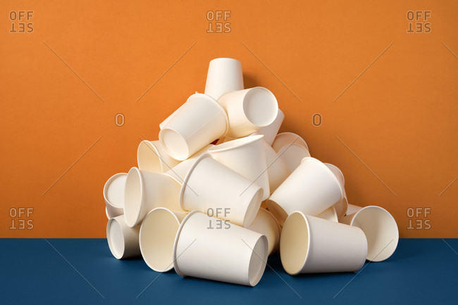 Stack of white paper drinking cups on orange and blue background.