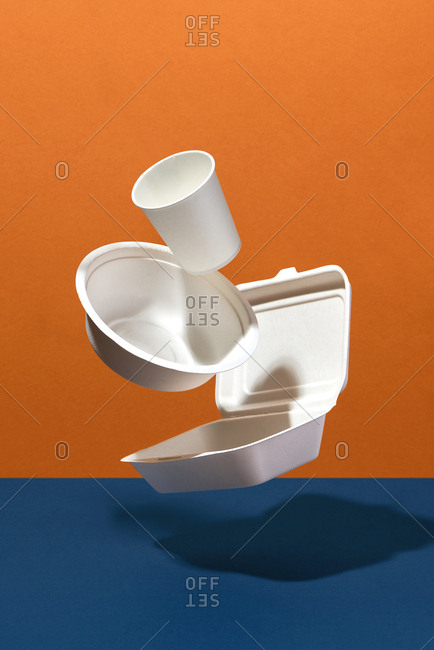 Eco friendly disposable dishes, cups, bowls on orange and blue background.recycling concept