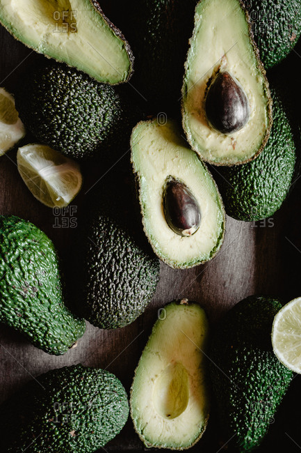 Closeup photo of raw whole and sliced avocados in a wooden box.