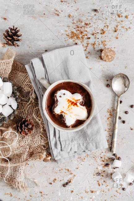 Gingerbread marshmallow on hot chocolate in a mug on a napkin with a metal spoon.