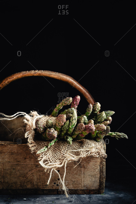 Raw asparagus in a wooden box in dark and moody room.