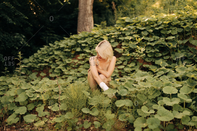 Topless Blond Woman With Broken Hand Squatting In Nature