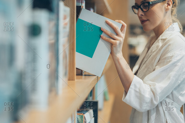 Pretty Caucasian woman picking a book from library shelf.