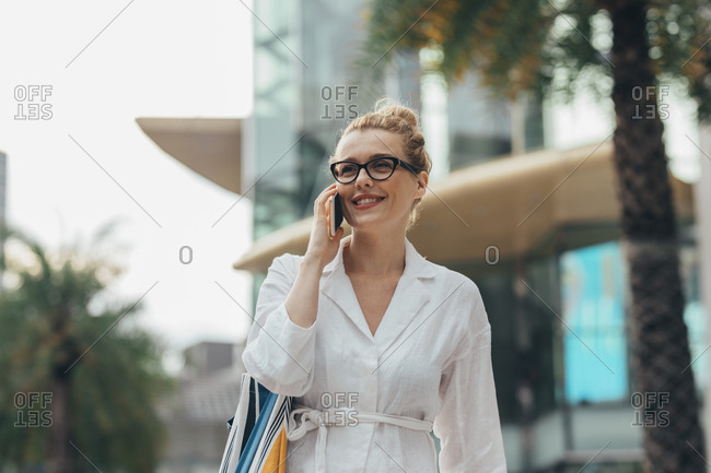 Beautiful smiling casual Caucasian woman standing outdoors on daylight and  talking on her smartphone.