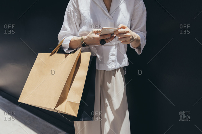 Unrecognisable cropped woman holding shopping bags and typing on her smartphone.